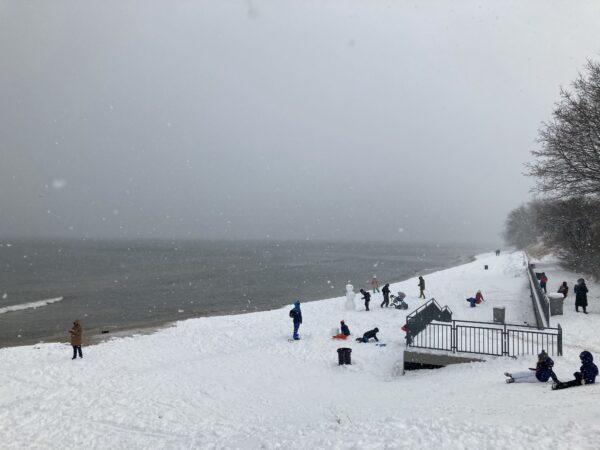 Brzeg morski pokryty sniegiem, morze, na sniegu balwan i ludzie zjezdzajacy na sankach